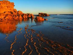 Red rock sunset (along_the_way) Tags: sunsetlight rockshelves beach water landscape sunset redrocks sky sea rock seren dusk ocean