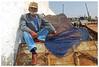 Man at the Docks - Essaouira, Morocco (TravelsWithDan) Tags: portrait outdoors docks city urban olderman essaouira morocco fishingnet fisherman sunglasses hat streetportrait canong9x framed