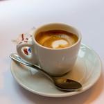 Kaffee mit schöner Crema mit Löffel und Zuckerbeutel auf Untertasse thumbnail