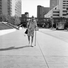 untitled (kaumpphoto) Tags: rolleiflex 120 tlr ilford bw black white city urban street man shorts pattern hat center summer cane satchel sidewalk shadow minneapolis