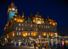 Balmoral Hotel at night (Rourkeor) Tags: 35mm 35mmzeisssonnartlens balmoralhotel carlzeiss edinburgh princesstreet rx1r scotland sony uk busstop capitalcity city clockface fullframe glow handheld historical lightshadows lights nighttime people reflections street christmastime sonyflickraward