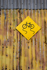 Bumpy Ride (Katrina Wright) Tags: dsc3216 corrugated sign bicycle unevensurface bumpyride cyclist weathered rusty beaten damaged yellow dents damage