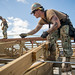 Seabees measure purlins on the roof of Tinian Elementary School.