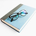 Book with reading glasses on white background