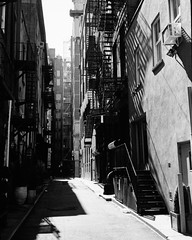 Great Jones Alley (colinpoe) Tags: citystreets bw 35mm blackandwhite cityscape urbanlandscape urbanite gothamist zonefocus fireescape shadows alley manhattan nyc greatjonesalley kodakxx kodak5222 rollei35s