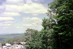 71-141 (ndpa / s. lundeen, archivist) Tags: nick dewolf nickdewolf color photographbynickdewolf 1975 1970s film 35mm 71 reel71 hanggliding hangglidingfestival franconia franconianotch newhampshire newengland mittersillalpineresort mittersill cannonmountain whitemountains worldcup competition hangglidingcompetition summer worldcupmeet meet mittersillworldcupmeet july sky bluesky clouds flight flying inflight hangglider hills mountains trees building hotel lodge parkinglot cars