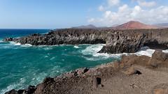 Waves (piotr_szymanek) Tags: lanzarote water sea ocean lava rock wave mountain landscape outdoor sky blue green beach cliff bay soil people 1k 20f 5k 50f 10k