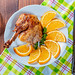 Chicken leg with oranges with knife and fork