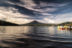Sunrise at Mount Fuji and Lake Kawaguchi - Kawaguchiko (Japan) (Andrea Moscato) Tags: andreamoscato giappone japan asia japanese 日本 nihon nippon asian light luce green shadow ombre prefecture attraction ombra site national nature natura natural naturale landscape paesaggio day sun sunshine white sky cielo nuvole clouds view vivid vista mountain montagna monte vulcano fujisan fujiyama volcano holy scenic unesco panorama water acqua lago lake freshwater reflection riflesso yamanashi dark deep fuji blue shore coast morning waves sunrise alba