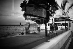 Going for a walk (iamunclefester) Tags: vacation holiday croatia krk otokkrk blackandwhite monochrome street boat ship ferryboat ferry sea water reflexion glass window windowpane pier mole balustrade pair couple tree leaves clouds rainy restaurant cafe café wall