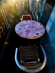 The Sunshine Table (Steve Taylor (Photography)) Tags: cafe restaurant tableandchairs window pink silver blue black gold glow lensflare perspective bike bicycle cycle