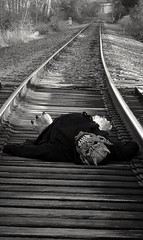Dead on the tracks, or is he !? (PhotoJester40) Tags: outdoors outside bnw blackandwhite blackwhite noirblanc posing railroadtracks gargoyle mask paradox amdphotographer human animal male