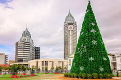 Christmas tree and city skyline in Mobile Alabama (CarmenSisson) Tags: christmastree mobile alabama downtown city christmas tree season seasonal cityskyline skyline mardigraspark rsabattlehousetower renaissanceriverviewplaza buildings cityscape outside outdoors day usa unitedstates us architecture spires architecturaldetail postmodern postmodernism skyscrapers