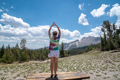 Young adult woman stands on a table doing a yoga pose in front of mountains in the Eastern Sierra Nevada of California (m01229) Tags: sierra awesome yogapose alpine nature water standing mammothmountain pose golden freedom trees mountainsarecalling girl conservation braidedhair lake mammothlakes woman amazing outdoors environment america experience beauty valley storm standup tranquil tiedyeshirt landscape scenic relax sunrise armsup mountains adventure dusksky monocounty sky mammoth dusk forest california lakes colorful glow sierranevada travel cloud hiking easternsierra park green usa tourism happy mountain