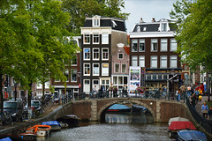 Lively Amsterdam (angelsgermain) Tags: canal water bridge street buildings houses people shops cars bikes trees lampposts ads sky reflections summer colours town amsterdam northholland netherlands