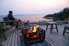Bidding The Sun Good-bye (peterkelly) Tags: digital canon 6d northamerica canada newfoundlandlabrador cavendish whitepoint shoreline shore coast coastline wooden wood deck fire flames lit heat table chairs chair sunset evening dusk beer cushion bandana