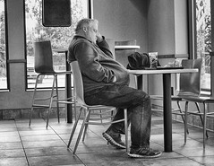 Chillin' (John Ilko) Tags: 500px relaxing lunch fastfood man cafe restaurant table chair x100f blackwhite acros