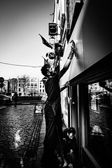 Shine on (Kieron Ellis) Tags: man men cleaning window building wall signs cobblestones reflection flag car apron candid street blackandwhite blackwhite