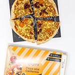Vegane Pizza mit Bohnen, Mais und Tomaten auf Schieferplatte neben Pizzakarton vor weißem Hintergrund thumbnail