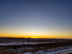 Along the road sunset 2 (darletts56) Tags: sky blue white yellow gold golden sun sunset dusk evening night grass blown fence fences field fields tree trees ice icy road prairie saskatchewan canada country farm silhouette post posts wire wires winter cold