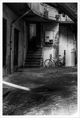 Un cortile (Outlaw Pete 65) Tags: cortile courtyard scale stairs bicicletta bicycle frigorifero fridge porte doors luce light biancoenero blackandwhite fujixe3 fujinon1855mm sarnico lombardia italia