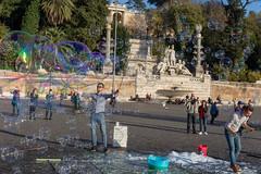 Mann in Jeanshose und Hemd macht auf öffentlichem Platz in Rom riesige Seifenblasen um Geld für seine Reise zu sammeln und wird von Passanten fotografiert, im Hintergrund Brunnen mit Statuen