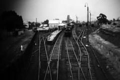 Narrandera Station in the Rain (oz_lightning) Tags: agfact18 australia canonpixmamg8150 filmscan nsw narrandera riverina buildings film platform railways scan slide station steam tracks trains bw newsouthwales aus halinasuper35x 35mmfilmcamera