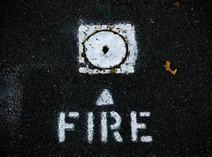 Fire in the Hole (Steve Taylor (Photography)) Tags: fireinthehole fire arrow firehydrant cover sign white tarmac newzealand nz southisland canterbury christchurch cbd city leaf round square