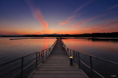 Floating (dim.pagiantzas | photography) Tags: bridge floating landscape water waterscape lake colors colorfull sunset orange blue sky clouds reflections peaceful atmospheric wood wooden railings lights ambient spot horizon trees nature mountains metal