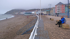 Aberystwyth Promenade. (Minoltakid) Tags: aberystwyth aber aberystwythpromenade llysybrenin ceredigion wales westwales welsh welshseaside welshheritage welshcoast welshseasidetown welshtown thewelshseaside town townphotography seaside seasidetown seasidecolours seasidephotography sea seafront seawall december winter people person sitting rx0 dscrx0 sonyrx0 sonydscrx0 theminoltakid minoltakid rossdevans rossevans ross uk unitedkingdom universitytown