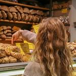 Eine Frau wählt ein Brot bei einem Bäcker auf dem Markt in Rom thumbnail