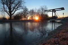 Sunrise after a cold clear night (Alex Borst) Tags: zonsopkomst zon zonnestralen sun sunrise apeldoorn apeldoorns kanaal lieren woudwegbrug sonne sonnenaufgang soleil lever du water canal clear sky blue frozen