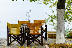The Ideal Spot (George Plakides) Tags: kastoria lake chairs tourism table tree cormorants reflections autumn leaves pavement