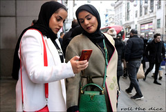`2509 (roll the dice) Tags: london westminster w1 westend oxfordstreet cold christmas mad sad fun funnt reaction shock people fashion pretty sexy girls urban unaware unknown streetphotography lights england uk classic art canon travel tourism tourists portrait strangers candid couple bargain sign natural colour happy out two shops shopping window blur arab muslim culture headscarf phone mobile louisvuitton makeup face