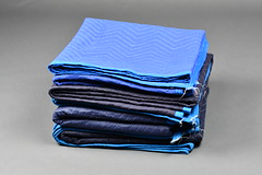 A Pile of Black and Blue Moving Blankets (hireahelper) Tags: furniture blanket moving pad mover relocate black blue grey shadow backdrop fabric pile