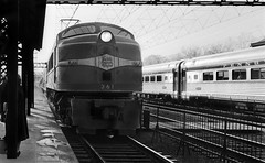 New Haven Railroad GE EP-4 Motor # 361, with its passenger train is seen while entering a station platform area, as the Pennsylvania Railroad Senator is seen on the opposite side platform track and it is heading in the opposite direction in 1955 (alcomike43) Tags: newhavenrailroad newyorknewhavenhartfordrailroadcompany trains railroads passengertrains regionaltrains localtrains commutertrains pennsylvaniarailroad thesenator station depot platform platformcanopy tracks rails ies roadbed ballast rightofway jointedsectionrail tieplates anglebars spikes electrification catenary catenarysupportstructure budd lightweightpassengercars stainlesssteelpassengercars passengercars hairpinfence pantograph engines locomotives motors electricengine electriclocomotive ep4class generalelectric streamliner ge 361 photo photograph negative bw blackandwhite old historic vintage classic
