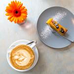 Kürbiskuchen mit Kernen und Puderzucker verziert auf einem grauen Teller mit einer Tasse Cappuccino und einer orangenen Gerbera thumbnail