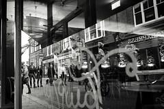 Giggling Squid Reflection (Bury Gardener) Tags: monochrome mono bw blackandwhite burystedmunds britain 2019 suffolk streetphotography street streetcandids snaps strangers candid candids people peoplewatching folks nikond7200 nikon uk british abbeygatestreet