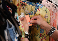 Merchant tags an article of clothing. Some of her jobs include tagging clothes, steaming clothes and deciding where to arrange the merchandise around the store.