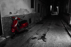 All Alone. Alcudia, Majorca. (MrWhippy99UK) Tags: street road building house path pothole tarmac wall windows living lights shadows spain spanish town city alcudia old coloursplash lonely bike motorbike vespa moped revgo red stand wheels mirror chrome holiday vacation photo photography canon 1300d efs engine metal seat black white blackwhite night time