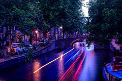 Nighttime boat travel along the canal (Brett of Binnshire) Tags: night streetlights powerboat netherlands sunset canalboat streetscene defender motionblur photographictechnique lights bluehour locationrecorded scenic architecture boat bridge amsterdam longexposure northholland nl canal magenta blue vivid color