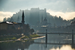 Mystical Salzburg... (echumachenco) Tags: salzburg austria österreich nikond3100 city cityscape building house church steeple spire castle fortress festung hohensalzburg evangelischechristuskirche kollegienkirche cathedral dom bridge müllnersteg river water reflection salzach sky fog mist cloud sunlight shadow ray autumn fall november