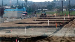 (Rich T. Par) Tags: pomona phillipsranch socal southerncalifornia losangelescounty lacounty constructionsite california palmtrees tree suburb dirt civilengineering sky frontloader tubes pipes heavyequipment road constructionvehicles parkinglot fence chainlinkfence civilengineers tractor truck