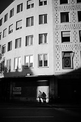 In the spotlight (iamunclefester) Tags: münchen munich street autumnstreetphotos autumn blackandwhite monochrome facade windows windowpane sunny bright sun shadows spotlight spot light castshadow hardshadow smartphone woman waiting shop shopwindow shopping bag