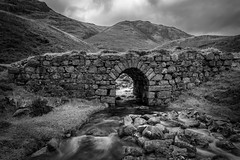 The Old Stone Bridge (bw) (stefanblombergphotography.com) Tags: blackandwhite clouds flow grass hill hillside landscape light mono mountain nature outdoor rock sky stefanblombergphotography stone stream water white black bw monochrome wwwstefanblombergphotographycom