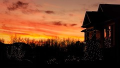 Holiday Sunset (Wes Iversen) Tags: christmas christmasdecorations christmaslights clichesaturday grandblanc grandreserve hcs nikkor18300mm automobiles autos cars holidays house houses reflections sky sunset sunsets trees vehicle windows