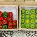 Zwei Körbe mit grünen Äpfeln und Paprika auf gefliestem Boden an Wand gestützt