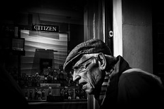 Citizen. (markfly1) Tags: chichester west sussex england market town candid image streetphoto black white watches man juxtaposition brand old gent elderly citizen jewellery shop window dim loght shade shadow hat cap wrinkles coat scarf slats shutters straps lines high contrast scene nikon d750 35mm manual focus lens