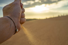 Bokeh Shot of a Hand dropping Sand in the Desert with Sunset in the Background