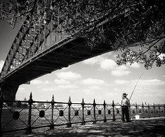 Fishing under the Sydney Harbour Bridge (missgeok) Tags: bridge outdoor bnw milsonspoint sydney newsouthwales australia lovethisplace fishing fishingrod blackandwhite nocolour monochrome composition hobby relaxing sydneyharbourbridge underthebridge steelfence harbour clouds